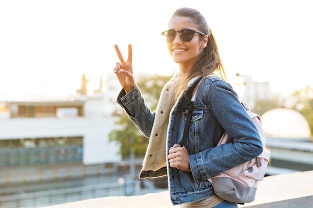 도시 거리에서 야외에서 걷고 재킷을 입고 아름 다운 젊은 여자