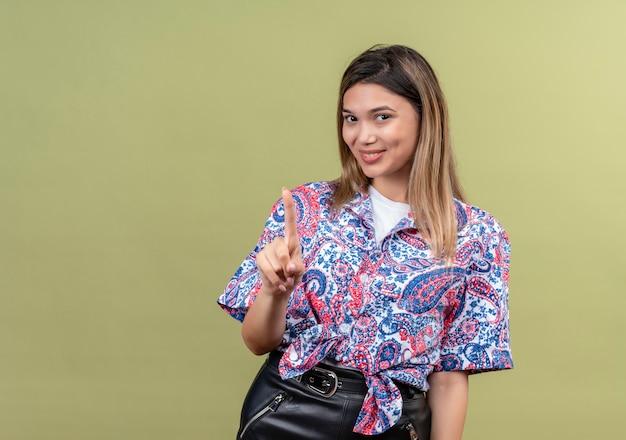 Una bella giovane donna che indossa la camicia stampata paisley sorridendo e indicando con il dito indice su una parete verde