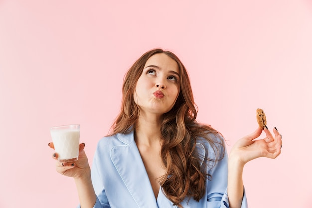 Красивая молодая женщина в пижаме, стоящая изолированно на розовом фоне, ест шоколадное печенье, пьет молоко