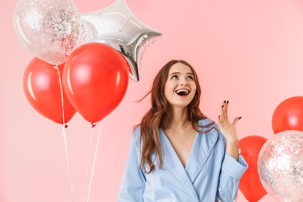 Beautiful young woman wearing pajamas standing isolated over pink background, celebrating with balloons