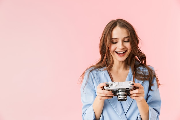 Beautiful young woman wearing pajamas standing isolated over pink background, holding photo camera