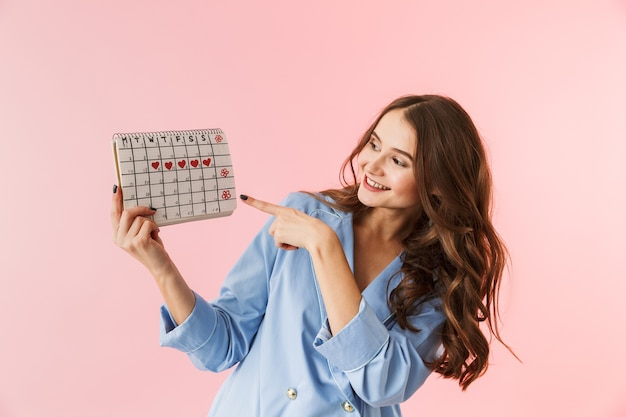 Beautiful young woman wearing pajamas standing isolated over pink background, showing menstrual calendar