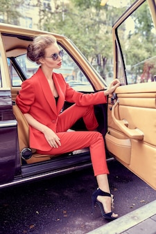 Красивая молодая женщина в красном костюме и солнцезащитных очках, сидя в ретро-автомобиле
