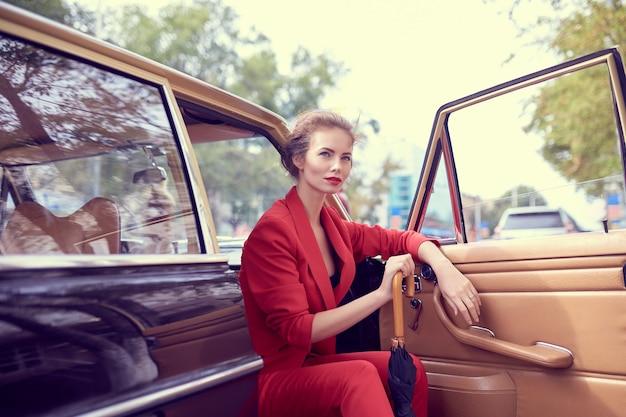 Красивая молодая женщина в красном костюме, держащая зонтик, сидя в ретро-автомобиле