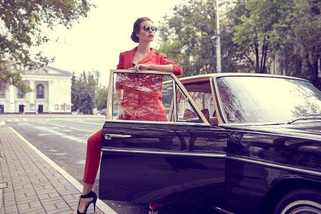 Красивая молодая женщина в красном костюме, стоя возле ретро-автомобиля