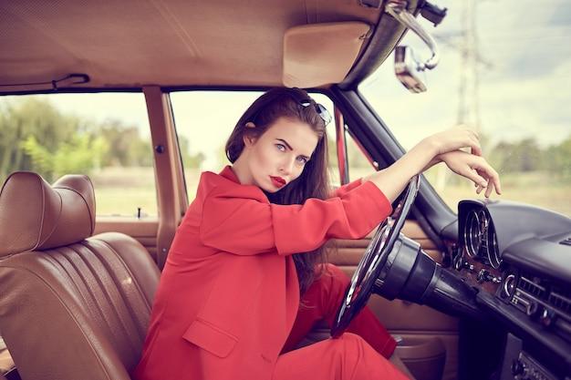 Красивая молодая женщина в красных костюмах сидит в ретро-автомобиле