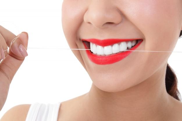 美しいアレンジされた歯と赤い唇を着ている美しい若い女性。彼女はデンタルフロスを使用して、歯の隙間に詰まっているすべての食べ物の粒子を掃除しています。口腔ケアの概念