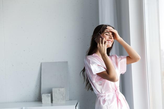 Красивая молодая женщина в халате, стоя у окна в спальне, разговаривает по мобильному телефону