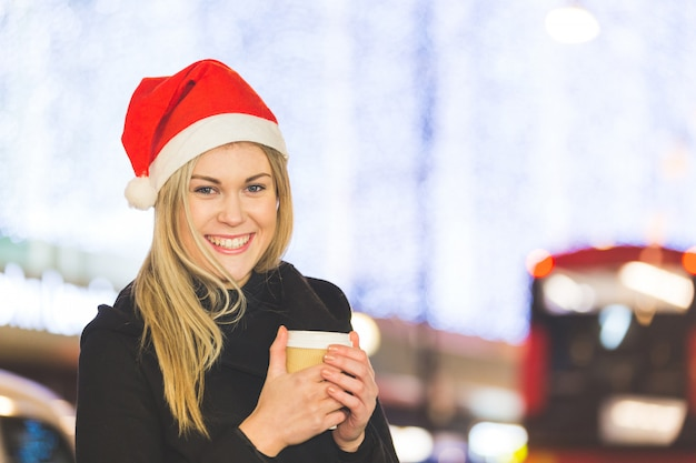 Beautiful young woman wearing santa hat in london