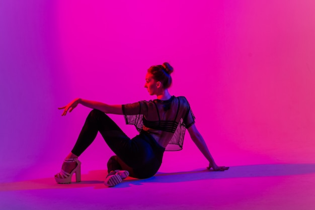 Красивая молодая женщина в сексуальных высоких каблуках и черной одежде во время танца в студии полюсного танца