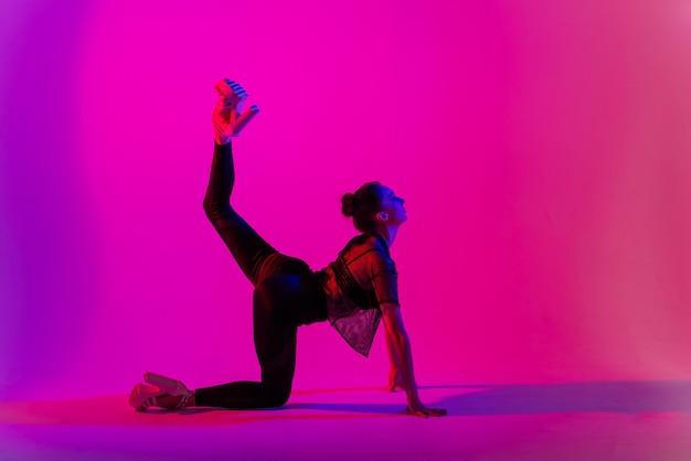 폴 댄스 스튜디오에서 춤을 추는 동안 섹시한 하이힐과 검은 옷을 입고 아름다운 젊은 여자