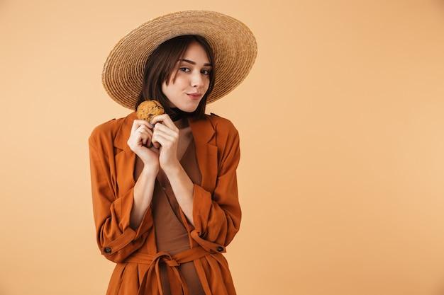 Красивая молодая женщина в соломенной шляпе и летнем наряде стоит изолированно над бежевой стеной и ест шоколадное печенье
