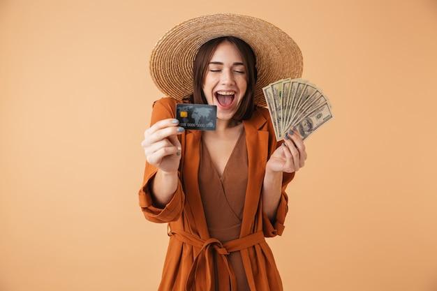 Красивая молодая женщина в соломенной шляпе и летнем наряде стоя изолированно над бежевой стеной, держа palstic кредитную карту, показывая денежные банкноты