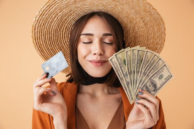 麦わら帽子と夏の衣装を身に着けている美しい若い女性は、ベージュの壁の上に孤立して立って、palsticクレジットカードを保持し、お金の紙幣を示しています