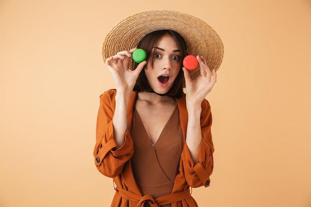 Красивая молодая женщина в соломенной шляпе и летнем наряде стоит изолированно над бежевой стеной и держит два миндальных печенья