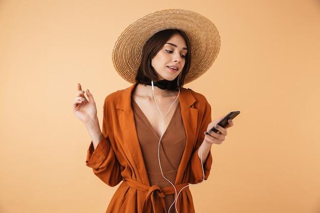 Красивая молодая женщина в соломенной шляпе и летнем наряде стоит изолированно над бежевой стеной, слушая музыку в наушниках и мобильном телефоне