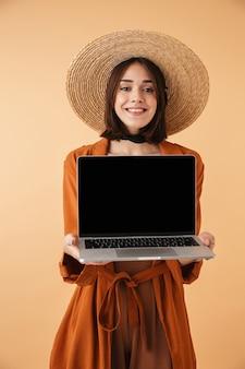 Красивая молодая женщина в соломенной шляпе и летнем наряде стоит изолированно над бежевой стеной, показывая пустой экран ноутбука