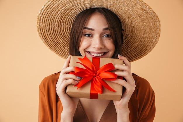 Красивая молодая женщина в соломенной шляпе и летнем наряде стоит изолированно над бежевой стеной, показывая подарочную коробку