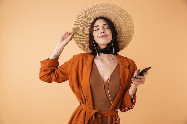 Красивая молодая женщина в соломенной шляпе, стоящая изолированно над бежевой стеной, слушает музыку в наушниках и держит мобильный телефон