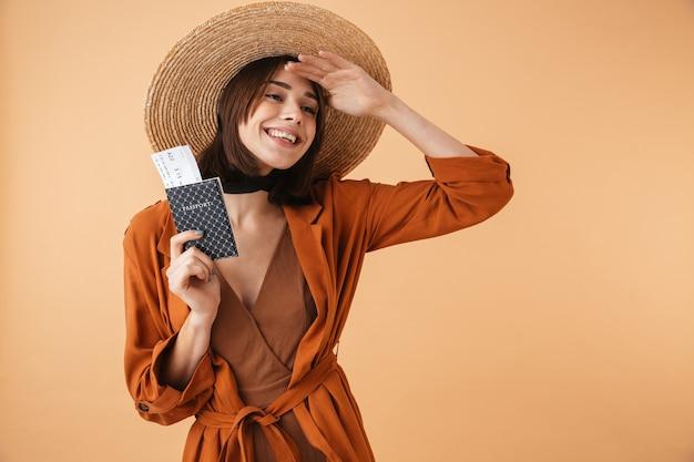 ベージュの壁に孤立して立っている麦わら帽子をかぶって、航空券とパスポートを示す美しい若い女性