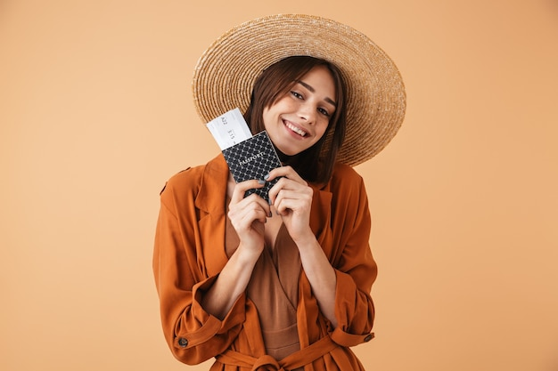 Beautiful young woman wearing straw hat and summer outfit standing isolated over beige wall, holding passport with flight tickets