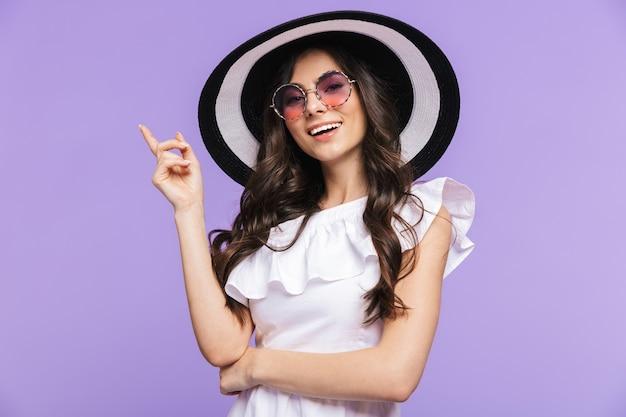 Красивая молодая женщина в летнем наряде стоит изолированной над фиолетовой стеной, указывая пальцем на копировальное пространство