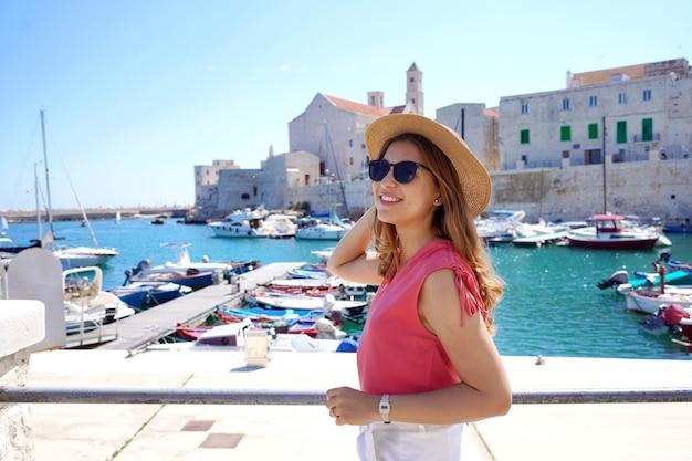 ジョヴィナッツォ、プーリア、イタリアの古い港の近くを歩いてサングラスをかけている美しい若い女性
