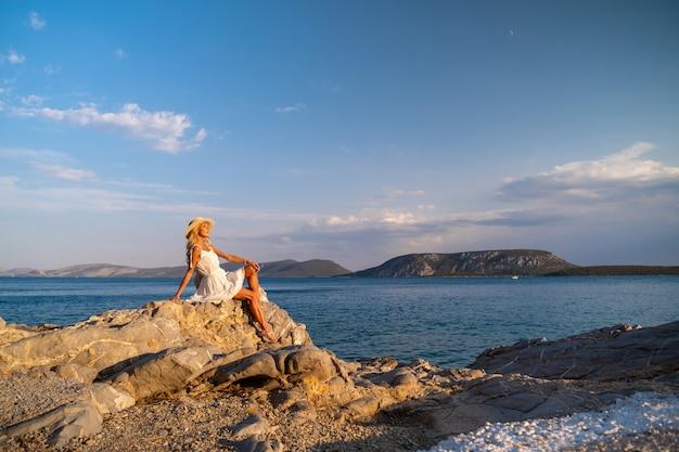 海岸沿いの白いドレスを着て岩に座っているトラウ帽子をかぶった美しい若い女性
