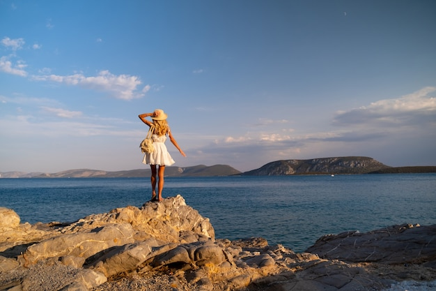 海岸沿いの白いドレスを着て岩に立っているトラウ帽子をかぶった美しい若い女性