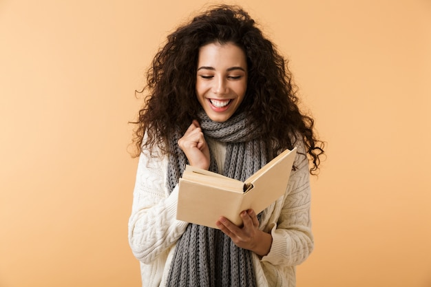 Beautiful young woman wearing winter scarf standing isolated over beige wall, reading a book