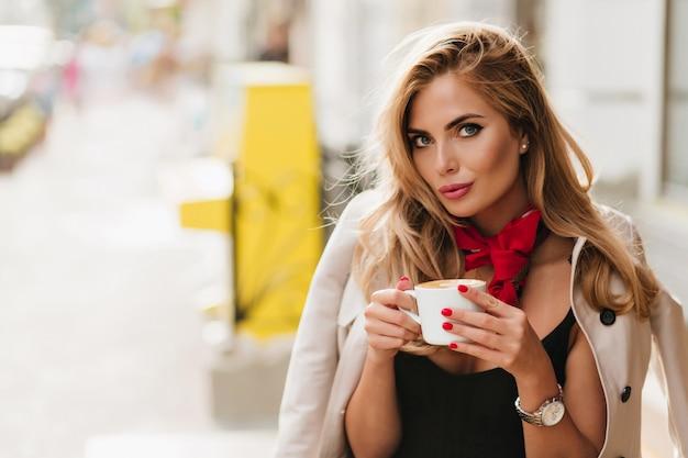 Красивая молодая женщина носит модные наручные часы, позирует на размытом фоне, пьет кофе после тяжелого дня