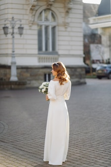 Beautiful young woman in wedding dress posing on the street in city