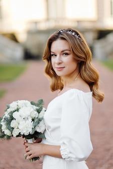 Bella giovane donna in abito da sposa in posa sulla strada in città