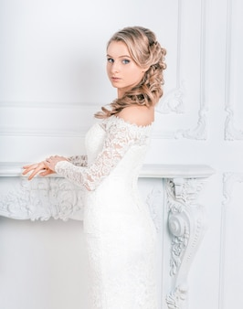 Beautiful young woman in wedding dress standing in bridal salon .