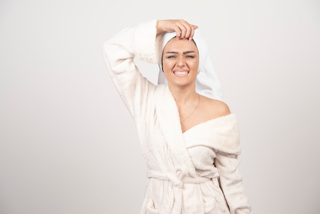 Beautiful young woman in a white bath robe isolated on white space