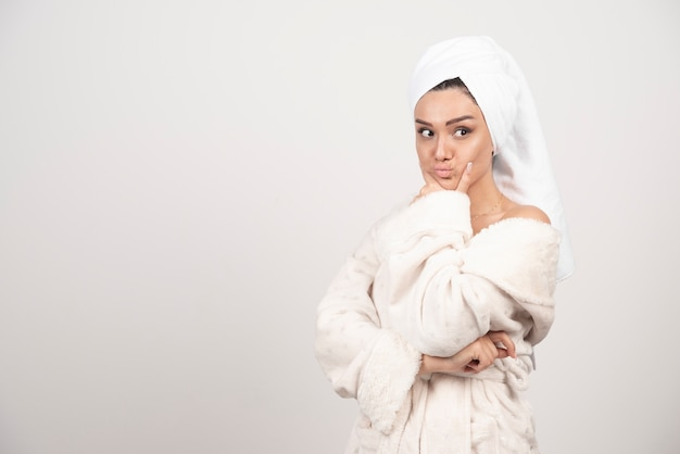 Beautiful young woman in a white bathrobe posing on a white wall