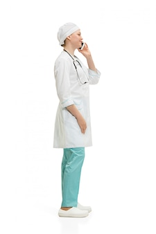 Beautiful young woman in white coat posing talking on the phone