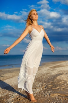 Beautiful young woman in white dress by the sea in the sun.