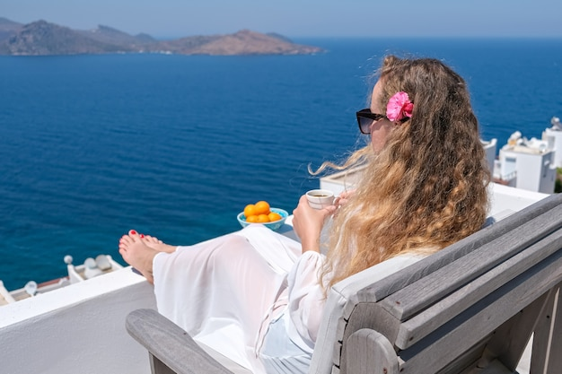 Beautiful young woman in white dress flower in hair and coffee cup sitting on white terrace balcony of house or hotel with sea view.