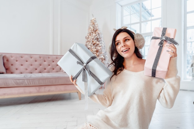 Beautiful young woman in white dress posing with gift boxes