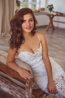 Beautiful young woman in white dress smiling toning photo