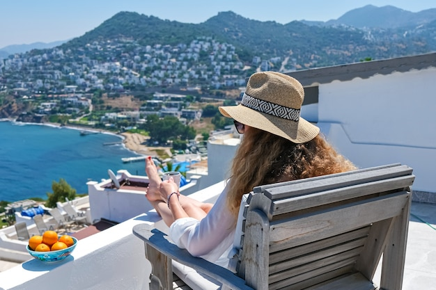 Beautiful young woman in white dress and straw hat and coffee cup sitting on white terrace balcony of house or hotel with sea view.