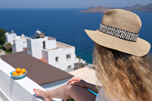 Beautiful young woman in white dress straw hat on white terrace balcony of house or hotel with sea view.