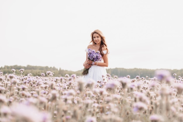 Beautiful young woman in a white dress with a bouquet of flowers in a field in summer in nature