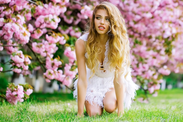 Beautiful young woman in white glamour dress on green grass in spring pink flowers bloom daisy flowers in meadow