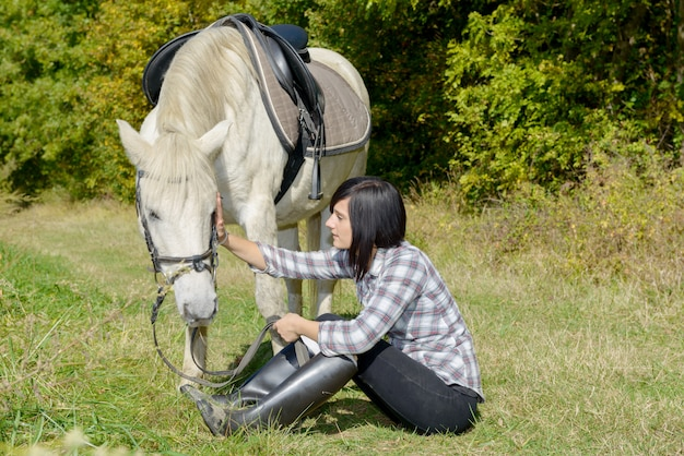 Beautiful young woman and white horse