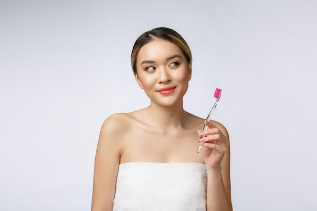 Beautiful young woman on white isolated background holds a toothbrush, asian