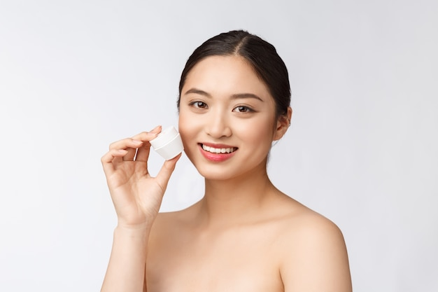 Beautiful young woman on white isolated wall holding cosmetic face cream, asian