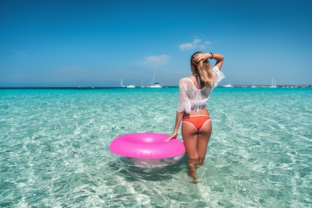 Beautiful young woman in white lace dress with pink swim ring in transparent sea at sunny day