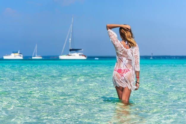Beautiful young woman in white lace dress with raised up arms in transparent sea at sunny day in summer